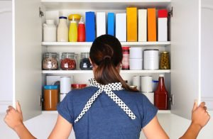 woman looking in pantry to take food inventory while social distancing