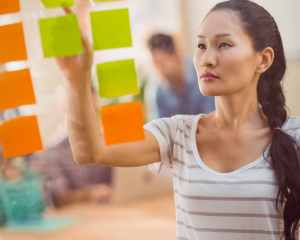 Woman putting Post-its on wall to help her prioritize